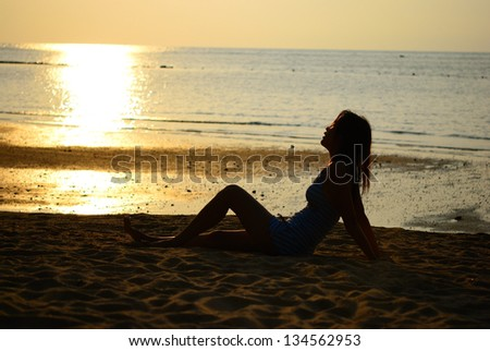 Silhouette of Asian woman sit an feel free on the beach in the evening
