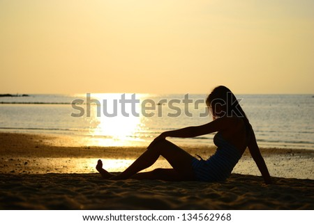 Silhouette of Asian woman take a rest after play on the beach