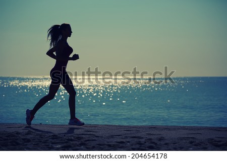 Silhouette of athletic female jogger with beautiful muscular figure running on the beach, female runner run along the sea, morning run on the beach, fitness and healthy lifestyle concept - stock photo