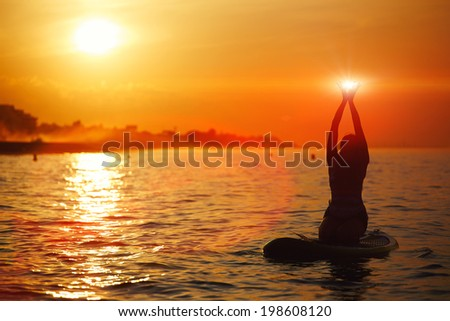 Silhouette of athletic girl holding hands in the sun during class of sup yoga - stock photo