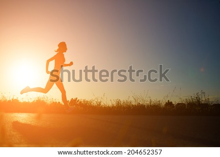 Silhouette of athletic girl running down the beautiful road at amazing orange sunset, female runner with muscular body at evening run,  fitness and healthy lifestyle concept