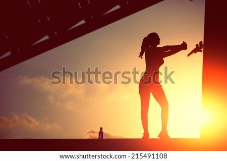 Silhouette of attractive female runner doing stretching exercise on beautiful sunset background, athletic female jogger silhouette against the sunset doing workout, woman fitness silhouette - stock photo