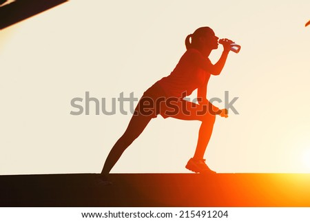 Silhouette of attractive female runner drinking water on beautiful sunset background, jogger with muscular body taking break after intensive evening training, sports advertising and healthy lifestyle - stock photo