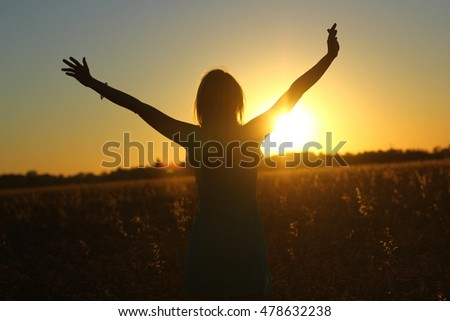 Silhouette of Attractive girl enjoy nature running, jumping, dancing in fields on sunset backlight. Young woman in dress having fun outdoor. Summer holidays concept.