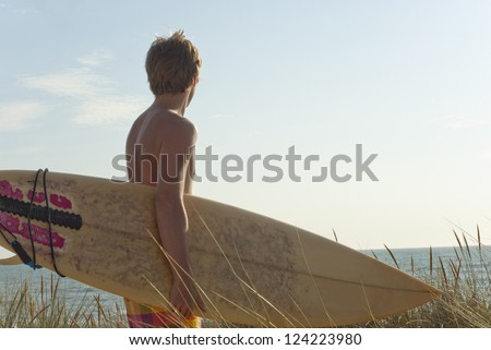 Silhouette of attractive young surfer holding surfboard while standing on dune looking at ocean to find the perfect spot to go surfing waves. Copy space in sky - stock photo
