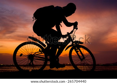Silhouette of backpacker ride mountain bike on bridge beside sea with sunset sky background - stock photo