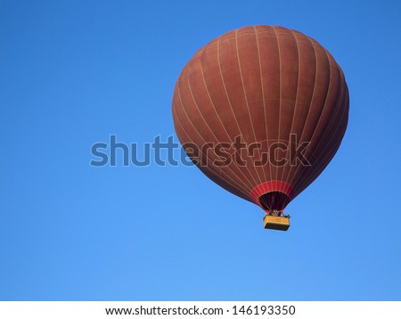Silhouette of balloon on blue sky background, landing at Sunrise - stock photo