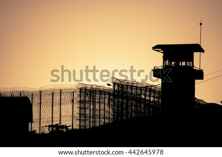 Silhouette of barbed wires and watchtower of prison in Neapolis, Crete, at sunset  - stock photo