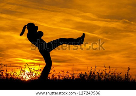 Silhouette of beautiful kick boxing girl exercising kick in the nature on sunny summer day.