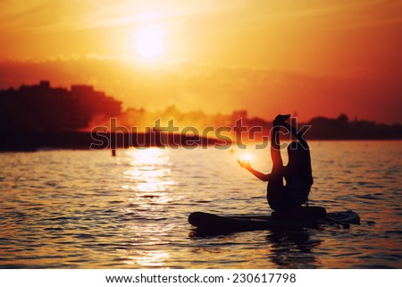 Silhouette of beautiful woman engage sup yoga at orange sunset, young attractive woman meditating yoga with amazing sunrise on background, spiritual concept inner light - stock photo