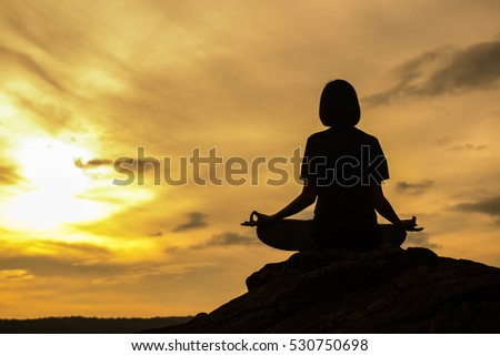 Silhouette of Beautiful Woman practicing yoga on stone water front at sunset