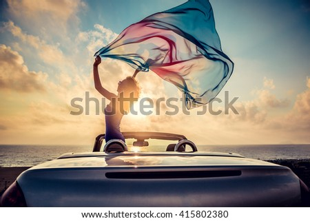 Silhouette of beautiful woman relaxing on the beach. Person having fun in cabriolet against blue sky background. Summer vacation and travel concept - stock photo