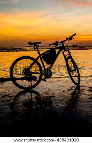 Silhouette of bicycle at jetty with sunset sky and sea background