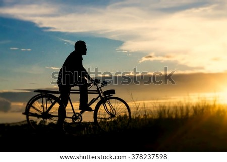 silhouette of bicycle with man - stock photo