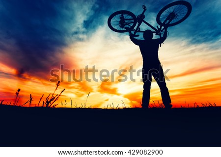 Silhouette of bicyclist rising bike and celebrating first place in contest