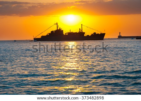Silhouette of big cargo ship in the port. Sea landscape against sunset - stock photo