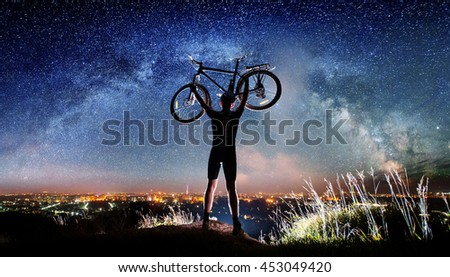 Silhouette of biker hold his bicycle above in the hands on the top of the mountain nearly city. Milky way and night city shining on the background  - stock photo