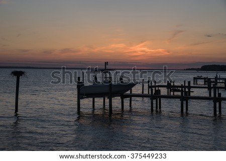 Silhouette of boat and dock at sunset