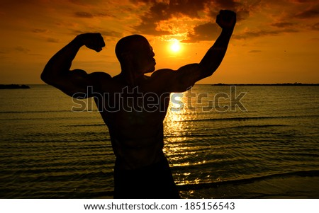 Silhouette of bodybuilder posing at the sunrise on the beach, training in the morning, strong man showing his muscles