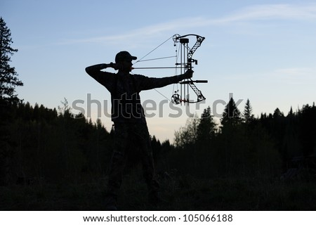 silhouette of bow hunter drawing bow back in woods - stock photo