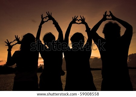 Silhouette of boy and girl forming their hands to heart form - stock photo
