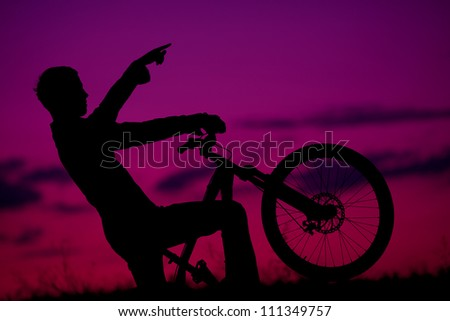 silhouette of boy cyclist in motion on the background of beautiful sunset (dawn) showing something ahead