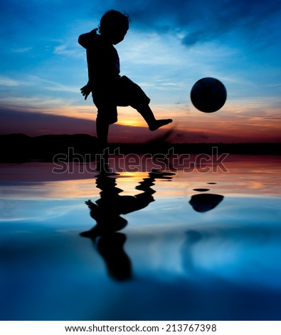 silhouette of boy kick the ball