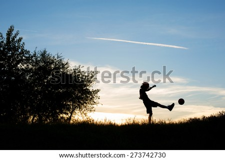 Silhouette of Boy Kicking a Ball Against a Blue Sky  - stock photo