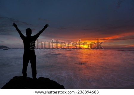 Silhouette of boy with hands raised to beautiful sunset