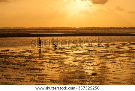 Silhouette of boys  at the beach during sunset