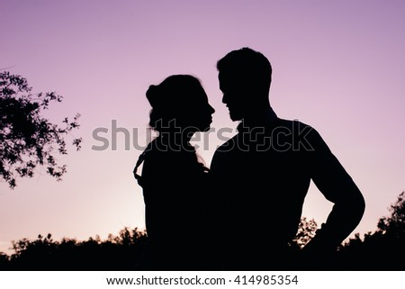 Silhouette of bride and groom against the evening purple sky
