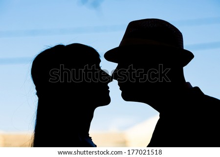 Silhouette of bride and groom kissing on the background of sky. - stock photo