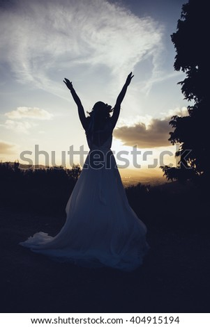 silhouette of bride in a landscape, with arms in the  air