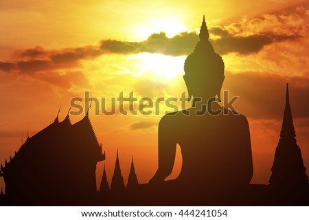 Silhouette of Buddha with sun shining from behind. - stock photo