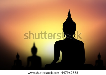 Silhouette of Buddha with sun shining from behind.