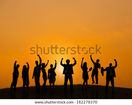 Silhouette of Business People Celebrating At Sunset - stock photo