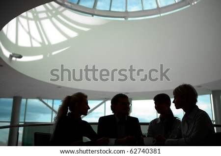 Silhouette of business people interacting with each other - stock photo