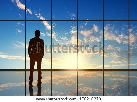 Silhouette of businessman against panoramic office window - stock photo