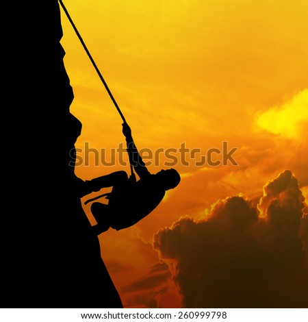 Silhouette of businessman climbs a mountain - stock photo