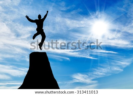 Silhouette of businessman jumping at the peak of the mountain on the background of the sunny sky