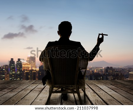 Silhouette of businessman sit on chair and hold a cigar and looking at the city in night. - stock photo