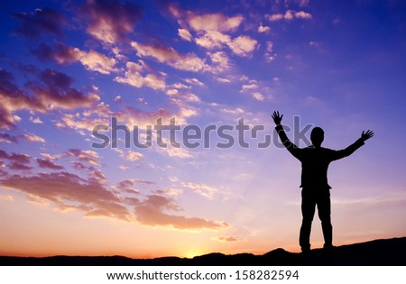 Silhouette of businessman standing on top mountain open arms looking at the sunrise or sunset - stock photo