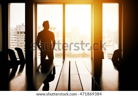 Silhouette of businessman thinking in meeting room with cityscape in background in evening sunlight.