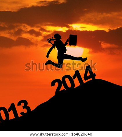 Silhouette of businesswoman is jumping over 2014 New Year - stock photo