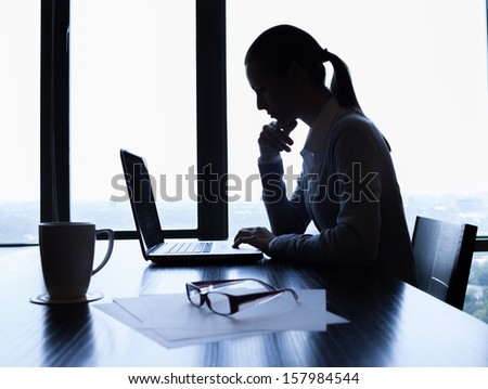 Silhouette of businesswoman using computer - stock photo