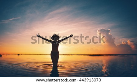 Silhouette of cheerful woman in the ocean at sunset