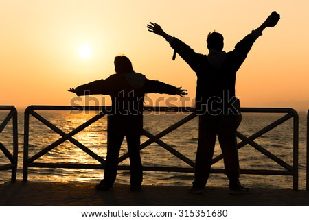 Silhouette of cheering young happy couple raising their arms to sunrise at sea