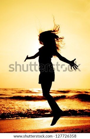 silhouette of child jumping in sunset - stock photo