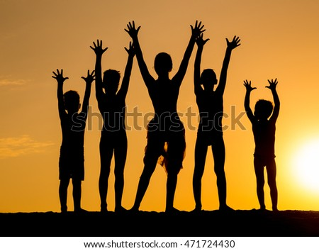 silhouette of children group against sunset
