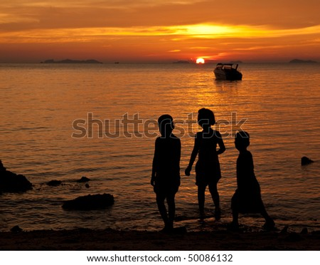 Silhouette of children playing on the beach at sunset